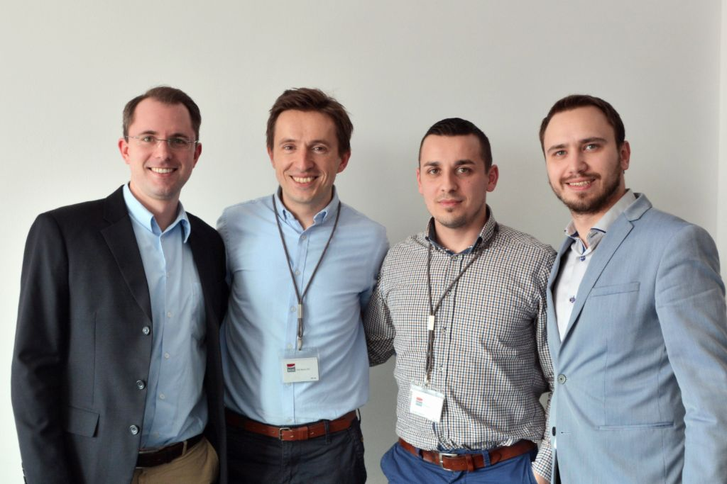 Four young project managers smile for the camera